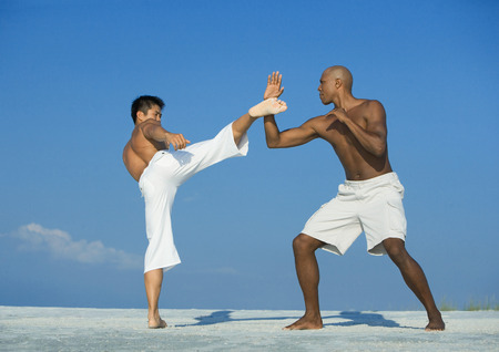 Two men practicing martial arts on beach