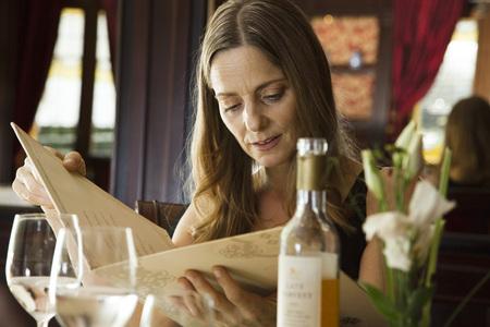 in low spirits: Mature woman looking at menu in restaurant