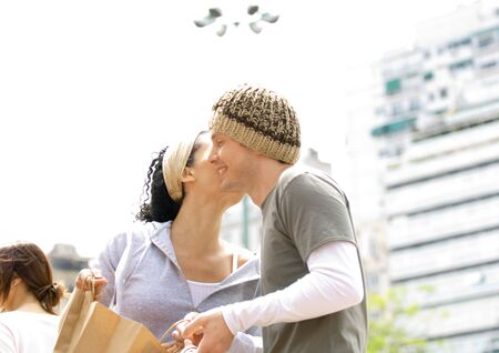 Young woman holding shopping bag and kissing young man on cheek LANG_EVOIMAGES