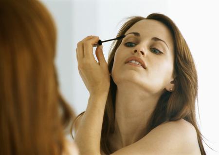 Woman applying mascara in mirror