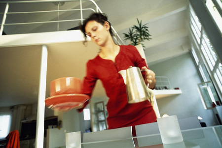 Woman holding coffee pot and cup