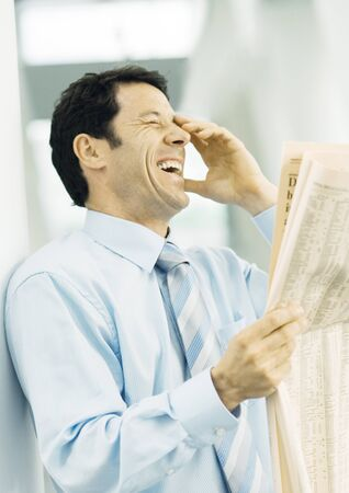 Businessman holding newspaper and laughing