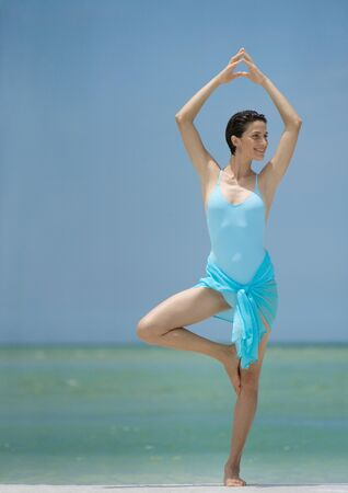 Woman standing on beach in yoga tree pose