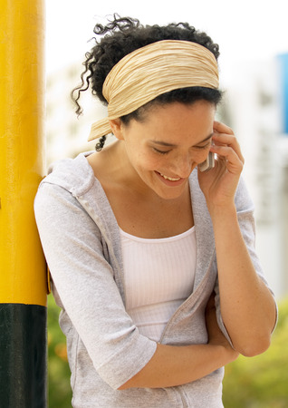 Young woman talking on cell phone, leaning against pole