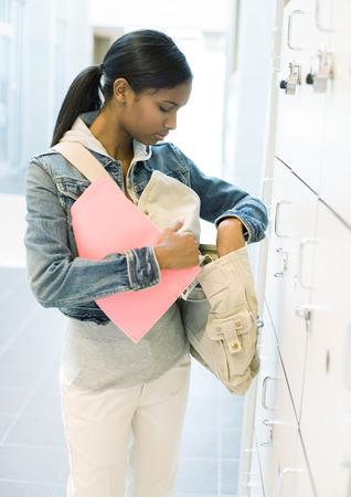 Teen girl standing by locker