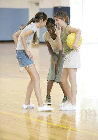 Three teen girls huddling in school gym