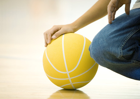 Teen boy crouching, holding basketball, close-up of hand on ball and knee