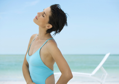 Woman on beach, head back and eyes closed