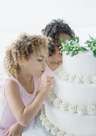 Girls looking at wedding cake LANG_EVOIMAGES