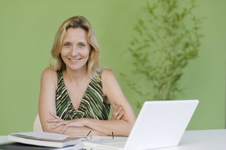 oneself: Mature woman with book and laptop computer, portrait