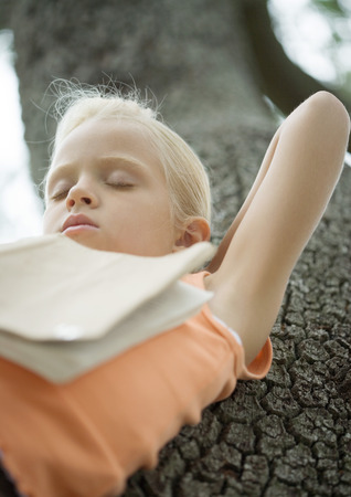 Girl in tree sleeping with book on chest