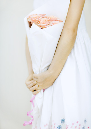 Girl holding bouquet of roses, partial view