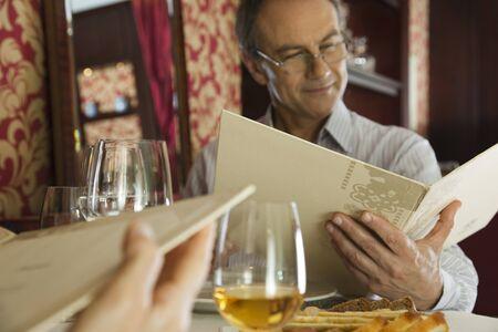 in low spirits: Mature man looking at menu in restaurant LANG_EVOIMAGES