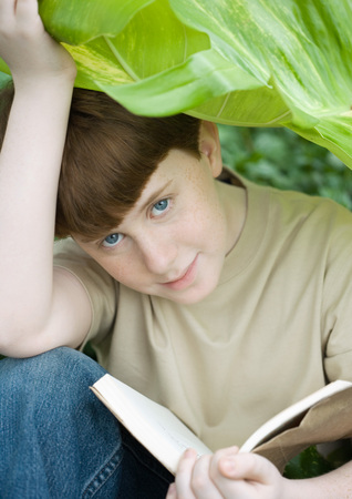 distractions: Boy reading under leaf