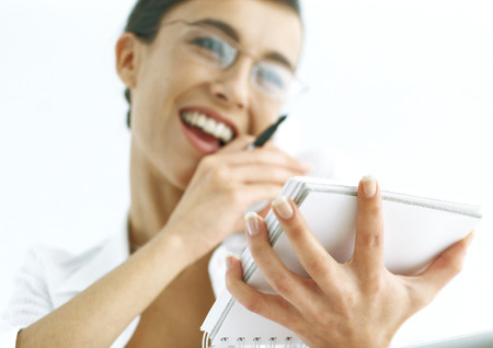 Woman talking on phone and holding notepad LANG_EVOIMAGES