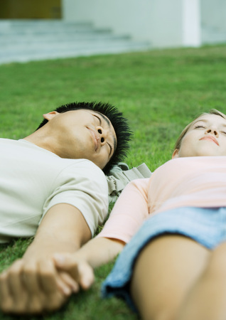 Young couple lying in grass, holding hands LANG_EVOIMAGES