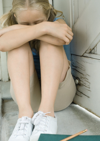 Girl sitting with knees up and head down