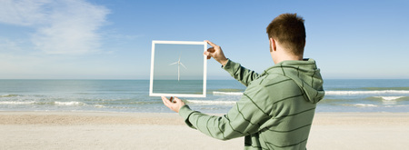 picture framing: Offshore wind turbine on horizon viewed from beach