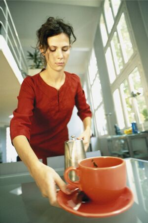 Woman picking up cup and saucer LANG_EVOIMAGES