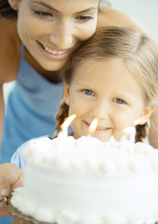 Mother and daughter with birthday cake LANG_EVOIMAGES