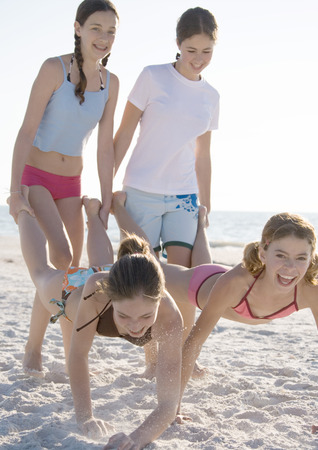 Preteen girls holding friends feet like wheelbarrows on beach LANG_EVOIMAGES