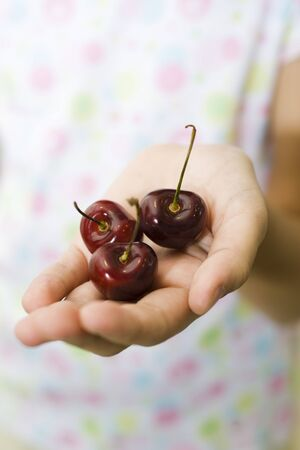 Cupped hand holding cherries