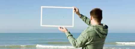 picture framing: Gulls flying above sea framed in picture frame held aloft by man on beach
