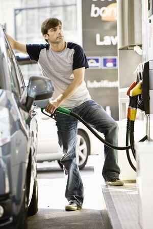 Man refueling vehicle at gas station LANG_EVOIMAGES