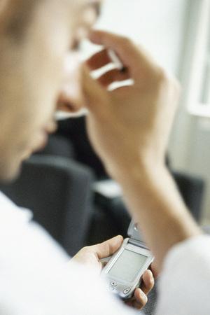 Man using cell phone, rubbing head
