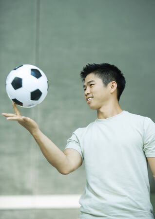 deftness: Young man balancing soccer ball on finger