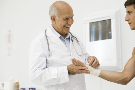 orthopedist: Doctor bandaging patients wrist
