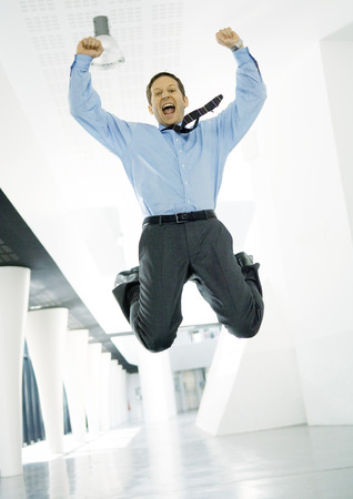 Businessman jumping with joy in lobby of office building LANG_EVOIMAGES