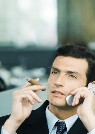 estereotipo: Hombre de negocios usando el teléfono celular y fumar cigarro LANG_EVOIMAGES