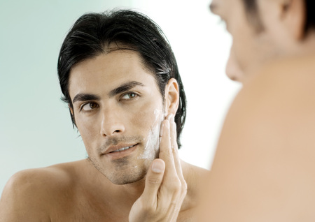 cremas faciales: Man putting on shaving cream in mirror LANG_EVOIMAGES