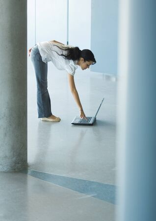Young woman bending over, pressing key on laptop LANG_EVOIMAGES
