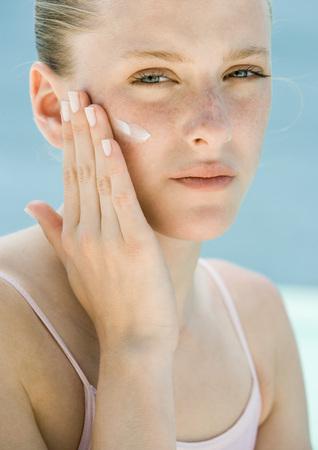 greased: Woman applying sunscreen