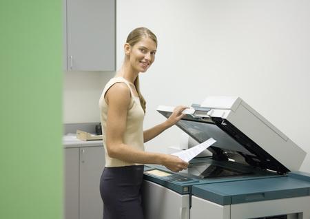 xerox: Woman making photocopies in office