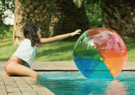 Girl sitting on edge of pool, reaching for beach ball in water