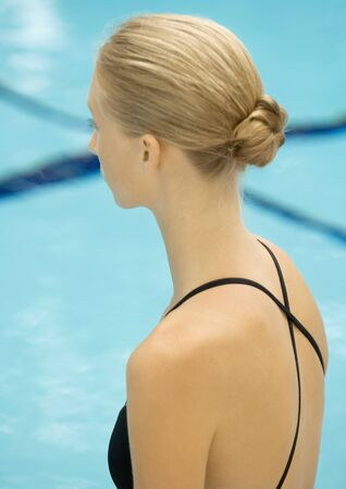Woman in bathing suit, looking at swimming pool, side view