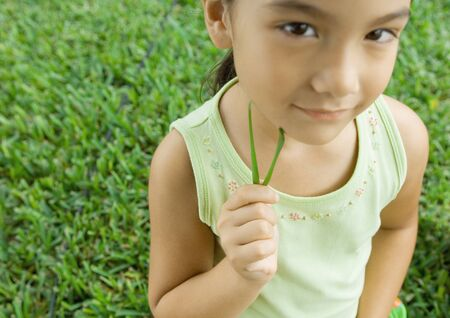 Girl holding blades of grass to cheek