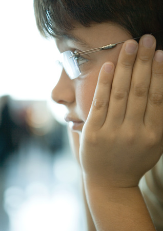 Boy holding head between hands, close-up of face