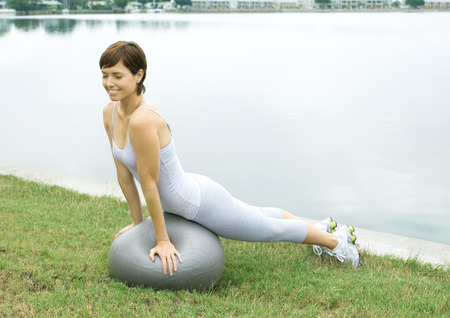 Woman exercising with fitness ball, next to lake