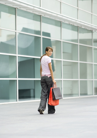 distractions: Teenage girl walking with shopping bags, looking over shoulder at camera LANG_EVOIMAGES