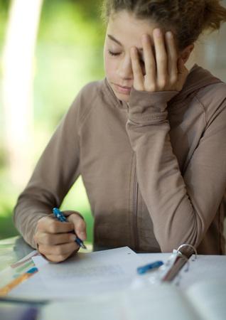 Preteen girl doing homework, holding head LANG_EVOIMAGES