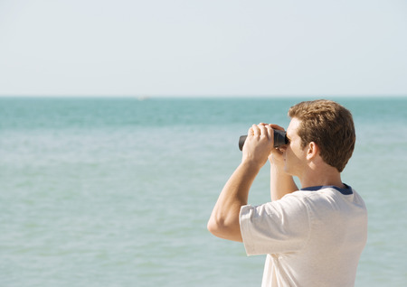 Man looking out to sea with binoculars
