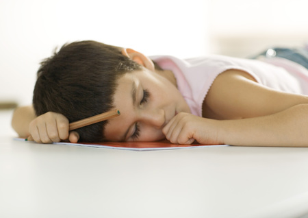 burned out: Child falling asleep with head on notebook and pencil in hand
