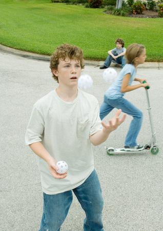 deftness: Children playing in suburban street, boy in foreground juggling