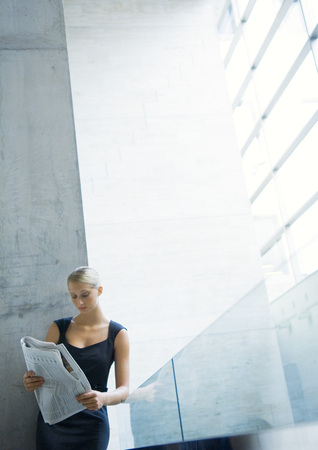 against the current: Businesswoman leaning against glass guard rail, reading newspaper