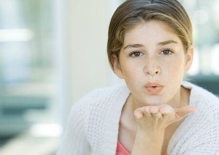 Preteen girl blowing kiss