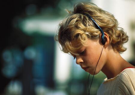 audition: Girl listening to headphones LANG_EVOIMAGES